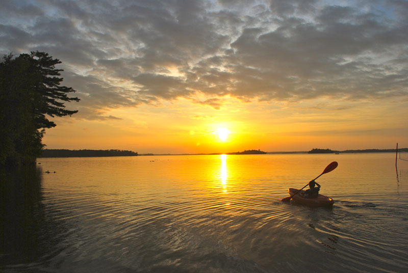 kayaker paddles into the sunset at resort beach