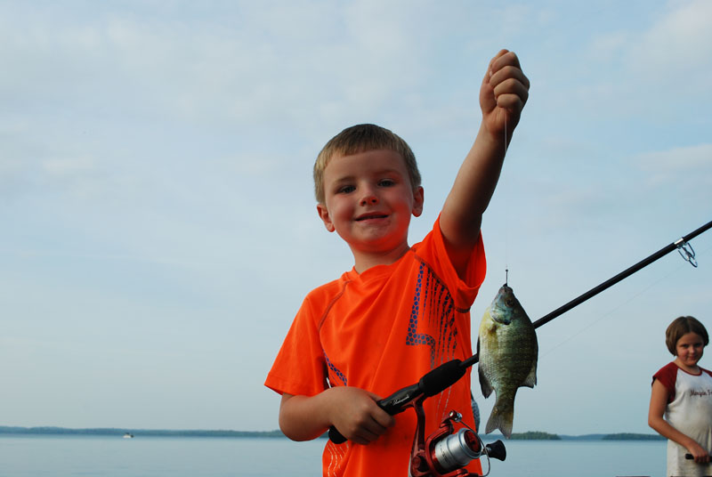 kid fishing for sunfish on dock