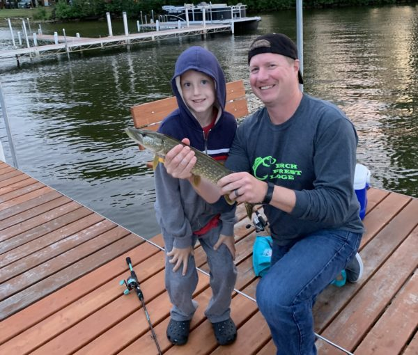 young boy catches northern pike on dock